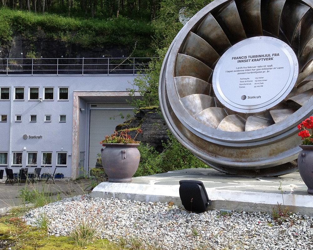 Innsett power plant reception building with turbine wheel and anniversary plaque.