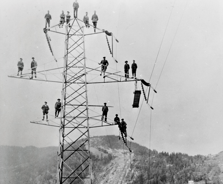 Black and white photo of men in power mast