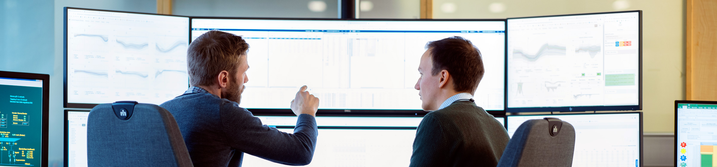 Two men discussing at computer screens