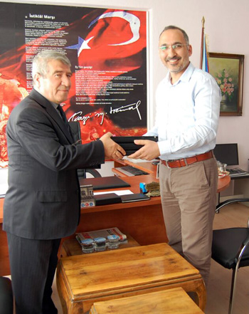 Bahadir Sezegen (right), who coordinates environmental and social issues for Statkraft in Turkey, hands over used and recycled Statkraft computers to Mahmut Karakaş, head teacher at Gemici Primary School in the city of Osmancik.