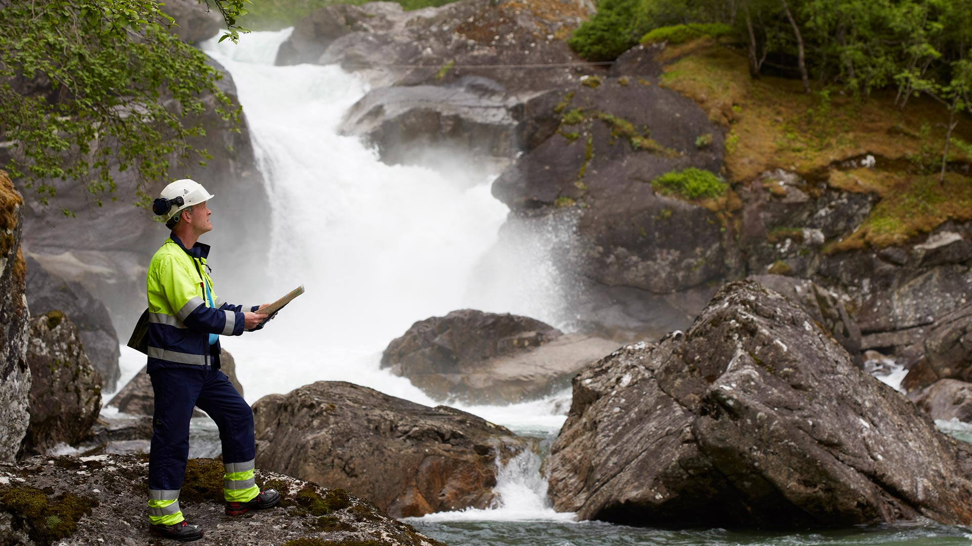 Man with helmet standing next to a waterfall
