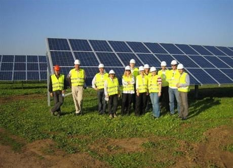 Men in yellow workjackets in front of solar panels